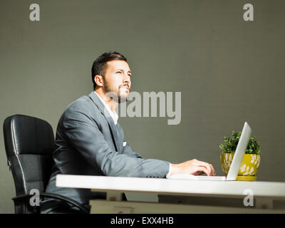 Young man sitting at desk and using laptop - Stock Photo