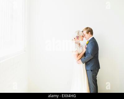 Newlywed couple embracing - Stock Photo