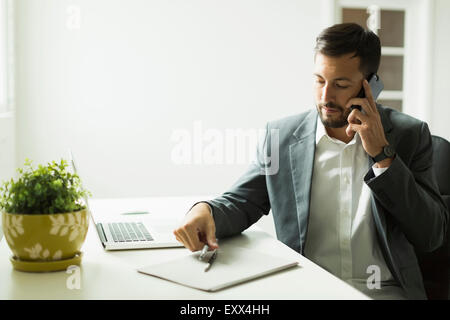 Young man sitting at desk and looking at laptop - Stock Photo
