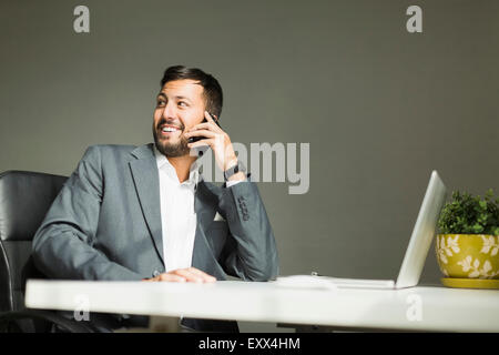 Young man sitting at desk and talking on phone - Stock Photo