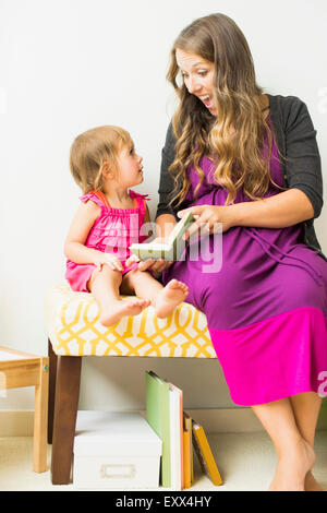 Mother reading to little daughter (2-3) - Stock Photo