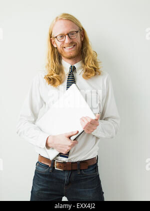Portrait of smiling man with laptop - Stock Photo