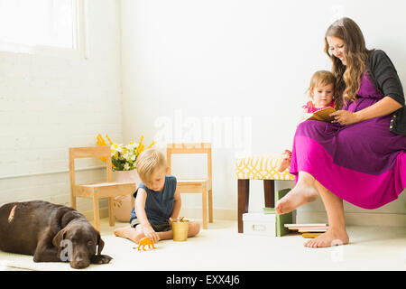 Mother reading to daughter (2-3) while son (2-3) playing on carpet - Stock Photo