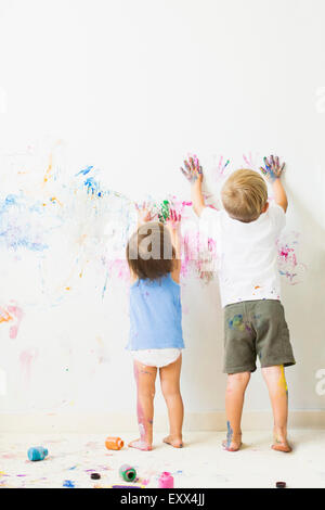 Children (2-3) painting on wall, rear view - Stock Photo