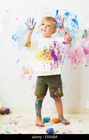 Boy (2-3) showing hands after painting on wall - Stock Photo