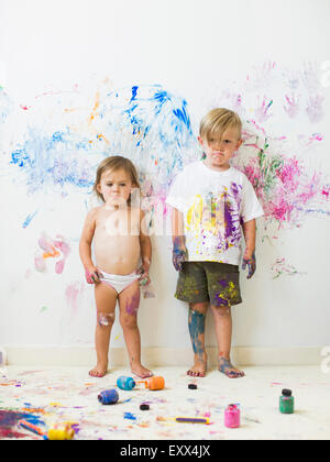 Children (2-3) painting on wall - Stock Photo