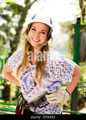 Portrait of smiling woman wearing helmet - Stock Photo