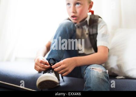 Boy (6-7) tying shoes - Stock Photo