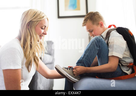 Mother helping son (6-7) tying shoes - Stock Photo