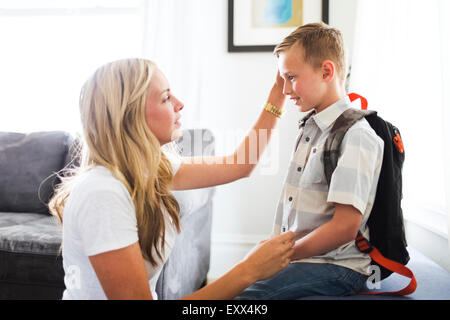 Mother preparing son (6-7) for school - Stock Photo