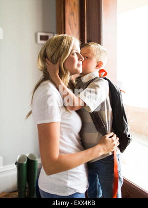 Son (6-7) kissing mother on cheek - Stock Photo