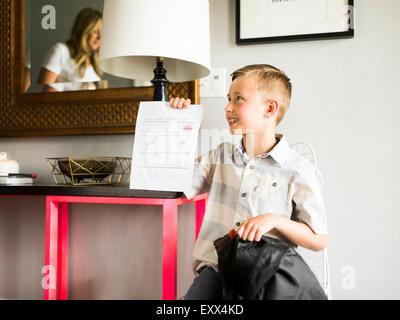 Smiling boy (6-7) showing schoolpaper - Stock Photo
