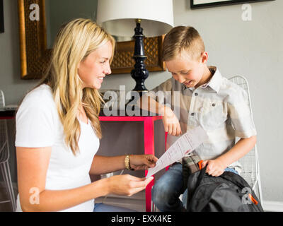 Smiling boy (6-7) showing schoolpaper to mother - Stock Photo