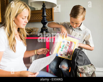 Boy (6-7) showing schoolpaper to mother - Stock Photo