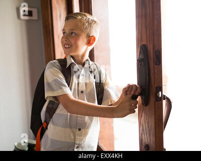 Smiling boy (6-7) leaving for school - Stock Photo