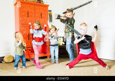 Children (2-3, 4-5, 6-7) wearing superhero costumes playing at home - Stock Photo