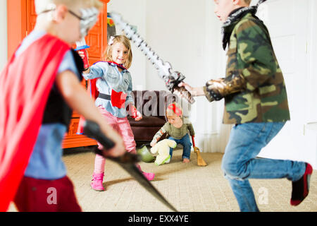 Children (2-3, 4-5, 6-7) wearing superhero costumes playing at home - Stock Photo