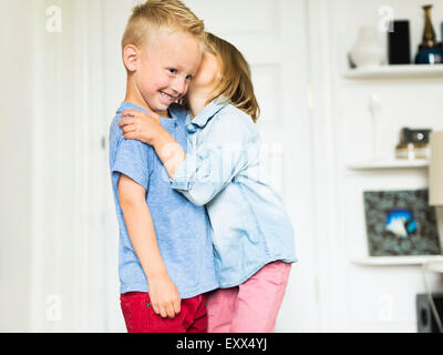 Little girl (4-5) whispering into brother's (4-5) ear - Stock Photo