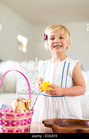Portrait of girl (2-3) holding candy - Stock Photo