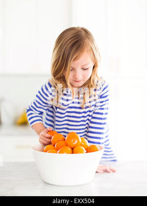 Girl (4-5) looking at oranges, smiling - Stock Photo