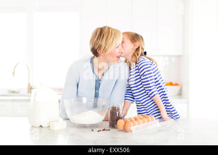 Girl (4-5) whispering into mom's ear - Stock Photo