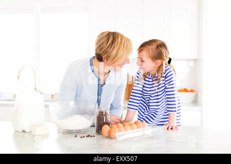 Girl (4-5) talking with mom in kitchen - Stock Photo