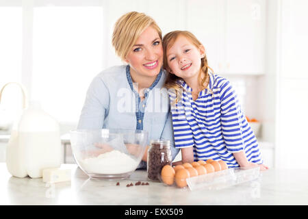 Portrait of girl (4-5) spending time with mom in kitchen - Stock Photo