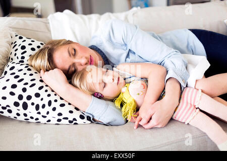 Mother and daughter (2-3) sleeping on sofa - Stock Photo
