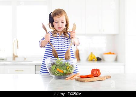 Girl (4-5) mixing salad - Stock Photo