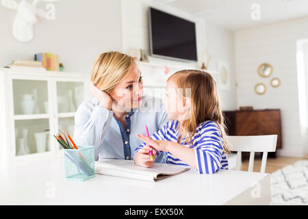 Girl (4-5) drawing with her mom - Stock Photo