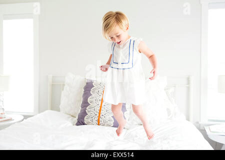 Girl (2-3) jumping on bed - Stock Photo