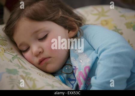Girl sleeping in bed - Stock Photo