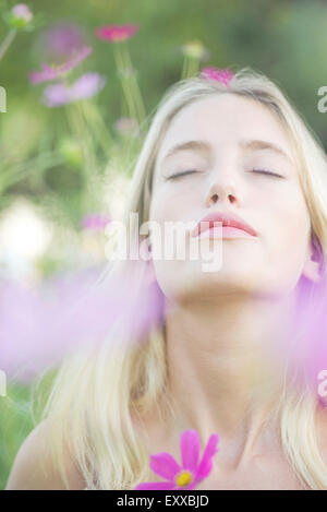 Woman overwhelmed by the sweet fragrence of blooming flowers - Stock Photo