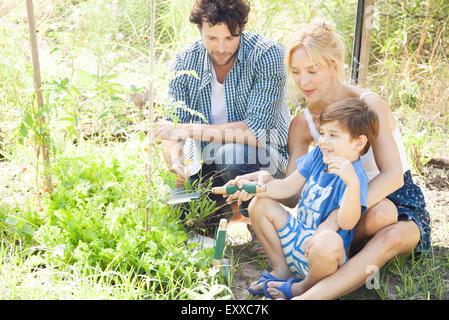 Parents teaching little boy how to garden - Stock Photo