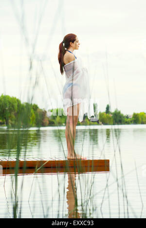 Woman standing at end of lake pier, looking at view - Stock Photo