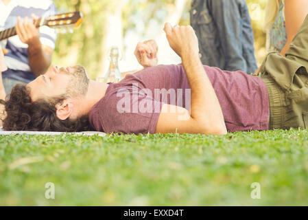 Man napping at picnic - Stock Photo