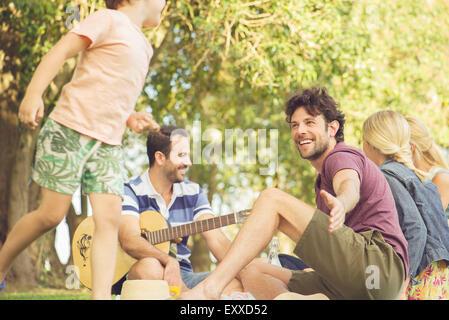 Man at picnic watching children play - Stock Photo
