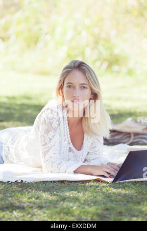College student using laptop outdoors - Stock Photo