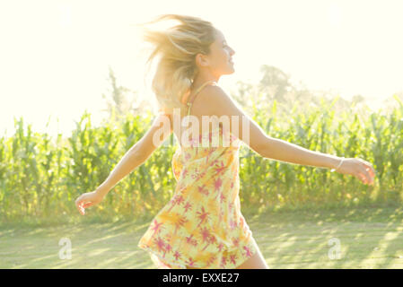 Woman running across open field - Stock Photo