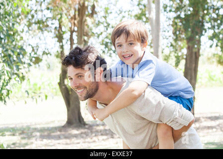 Father carrying young son piggyback - Stock Photo