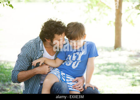 Boy sitting on father's lap - Stock Photo