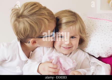 Boy kissing little sister's cheek - Stock Photo