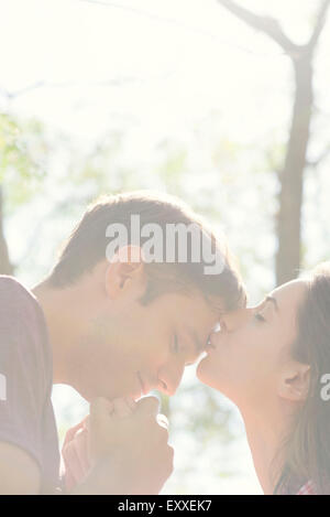 Couple together outdoors, woman kissing man's forehead - Stock Photo
