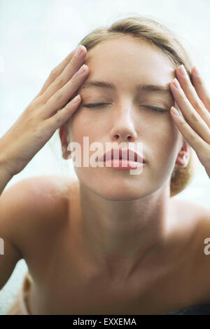 Woman relaxing in pool with eyes closed - Stock Photo