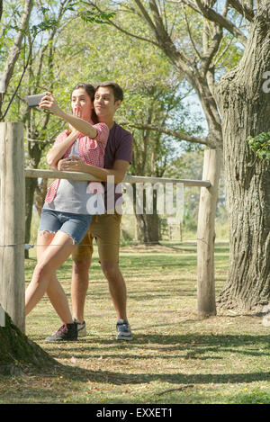Couple posing for a selfie in park - Stock Photo