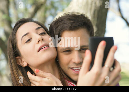 Couple posing for selfie outdoors - Stock Photo