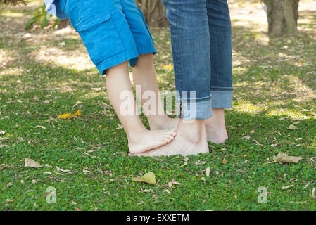 Little boy standing barefoot on father's feet, cropped - Stock Photo
