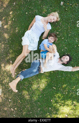 Young family with boy lying together on grass - Stock Photo