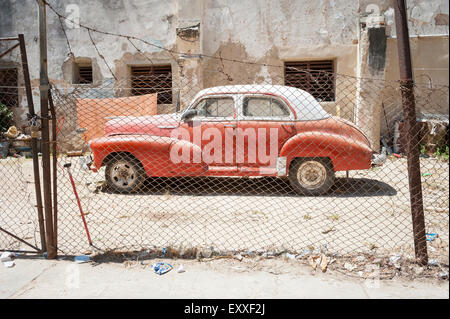 Vintage American car stands parked in the sun on a dusty lot in Centro, Havana, Cuba - Stock Photo
