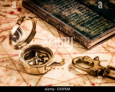 Still life about travel, journey, trip. Antique brass compass on a very old map with an antique book and  a ship' - Stock Photo